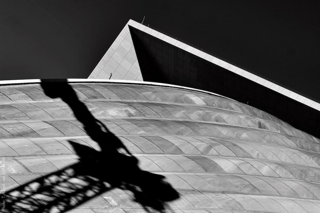 Shadow of a construction crane on the roof of the Cnit in the La Défense district of Paris